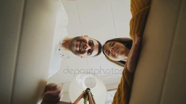 Mladý šťastný pár otevření krabici a nahlížela líbání po přemístění v novém domě
