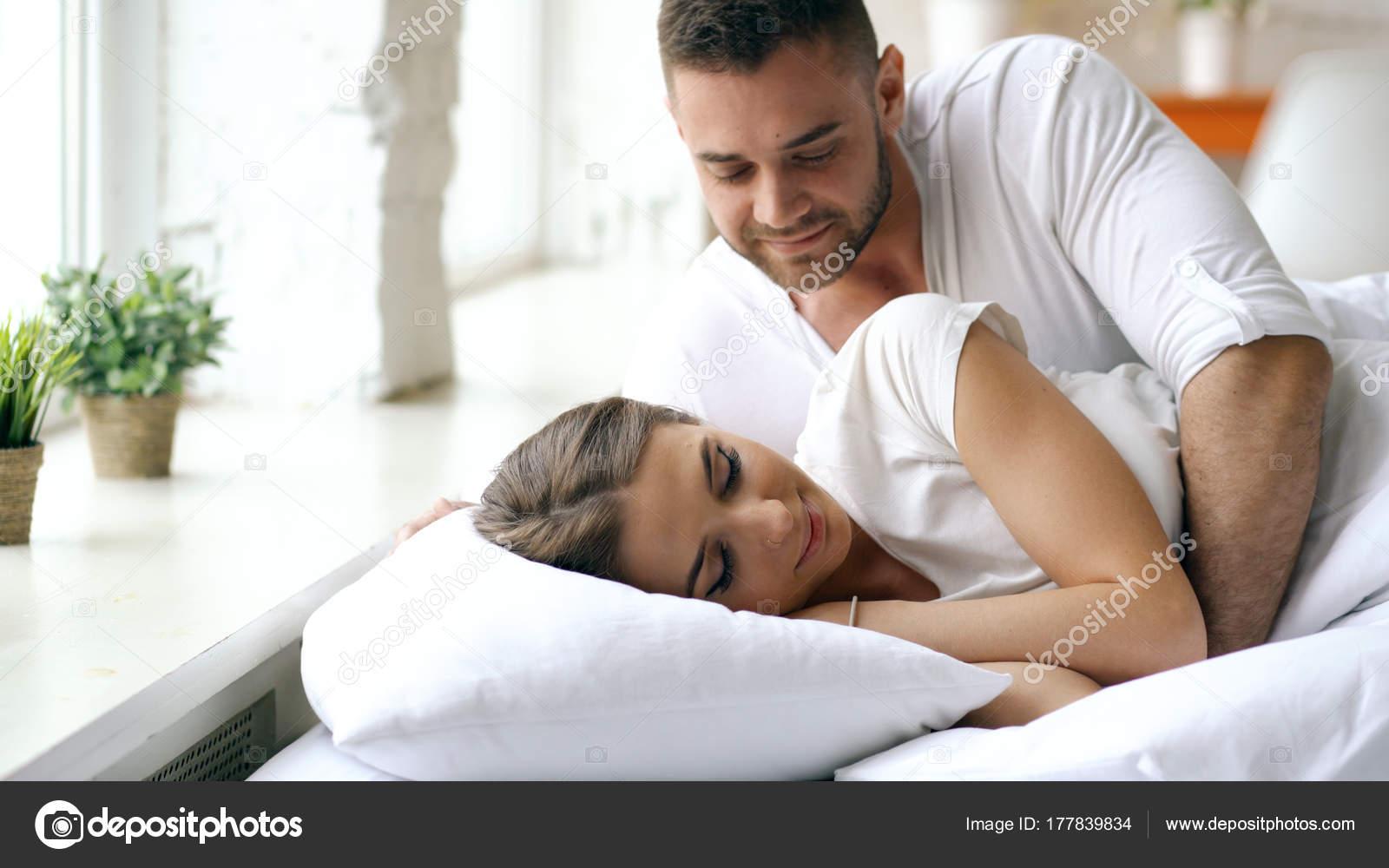 Giovane Coppia Bella E Amorevole Si Sveglia Al Mattino Uomo Attraente Bacio Abbraccio La Moglie A Letto Foto Di Silverkblack