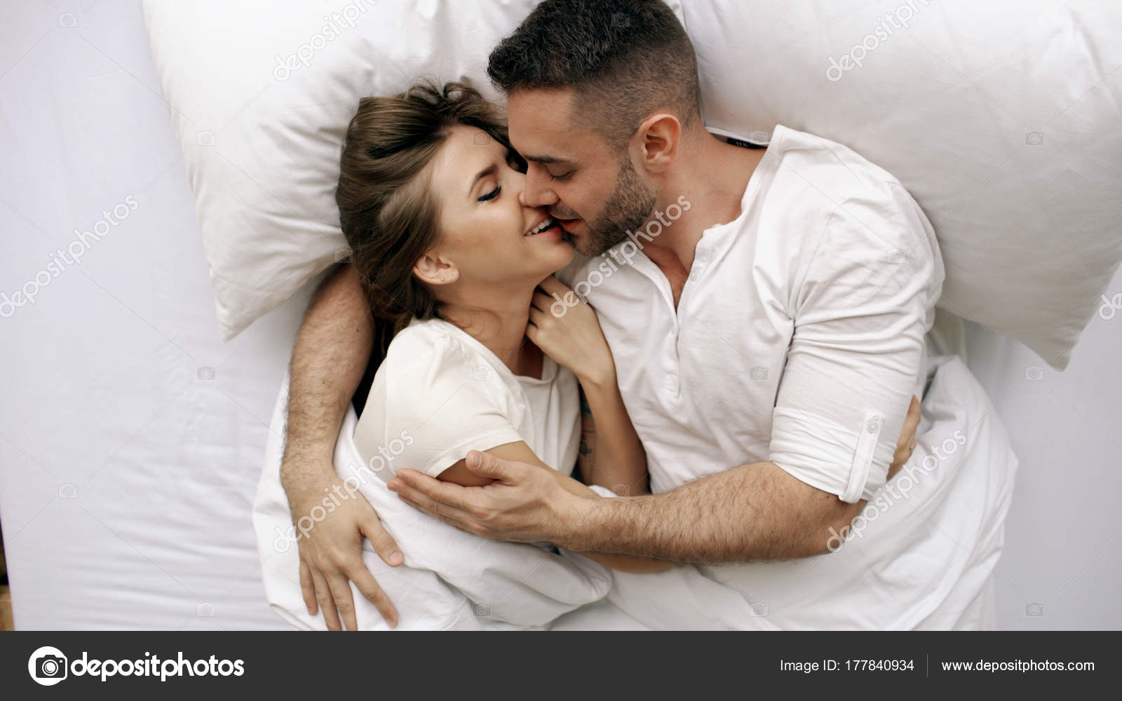 Young Beautiful And Loving Couple Kiss Hug Into Bed While Waking Up In The Morning