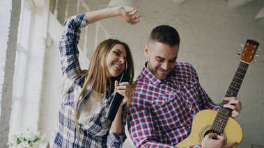 Funny happy and loving couple dancing and playing guitar. Man and woman have fun during their holiday at home