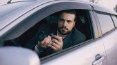 Mladí soukromý detektiv muž sedí uvnitř vozu a fotografování s fotoaparátem dslr