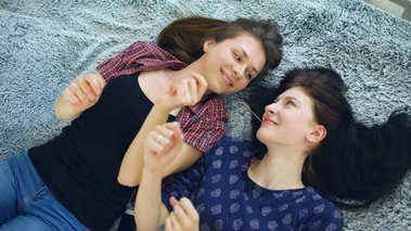 Top view of two beautiful girls in headphones listening music dancing and smiling while lying on bed