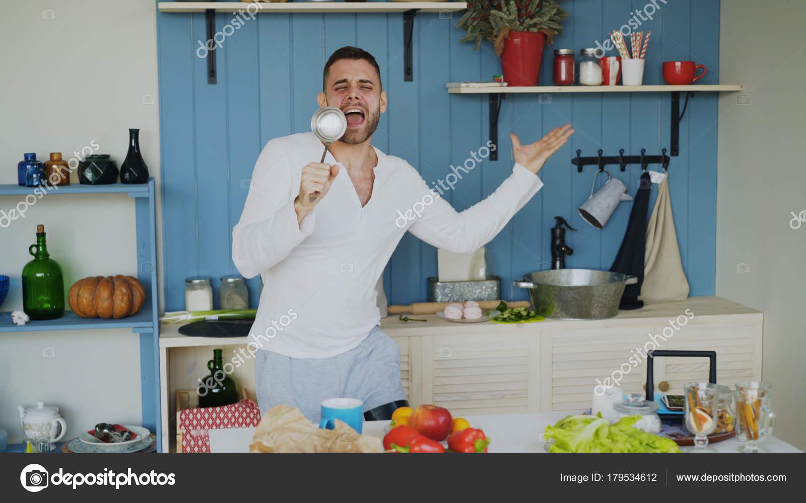Attraktive junge Mann lustig tanzen und singen mit Schöpfkelle beim ...