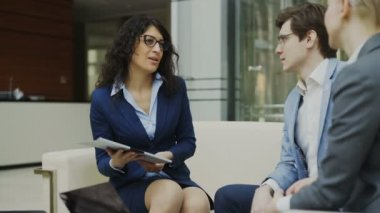 Businesswoman in glasses talking and duscussing future contract with business partners sitting on couch in modern office