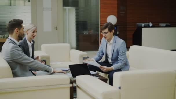 fröhlicher Geschäftsmann diskutiert mit Geschäftspartnern auf Sofa im modernen Büroflur über Finanzberichte