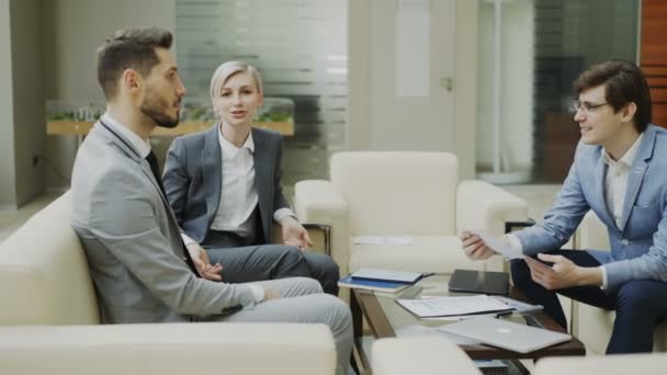 Panning shot of businessman discussing financial reports with female and male business partners sitting on sofa in modern office hall with