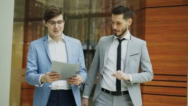 Két üzletember kollégák séta, és megvitatni a teremben modern office dokumentumok