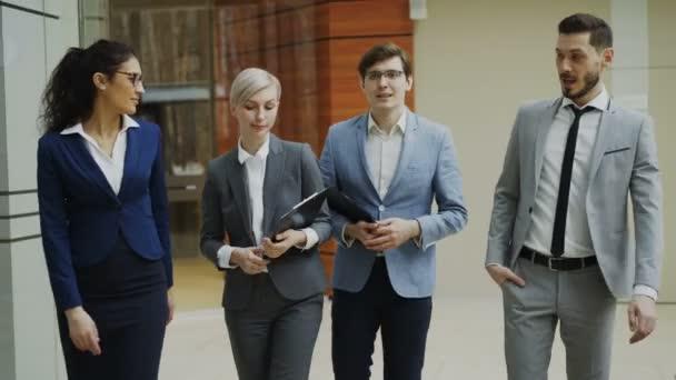Stedicam střílel skupina mladých podnikatelů mluví a procházky ve vestibulu