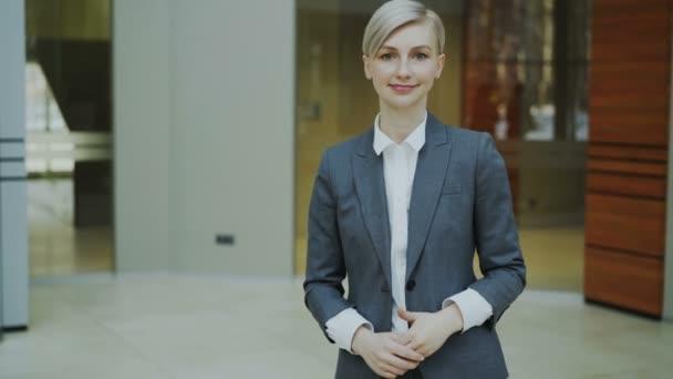 Portrét úspěšná podnikatelka blondýna usmívá a při pohledu do kamery v moderní kanceláři