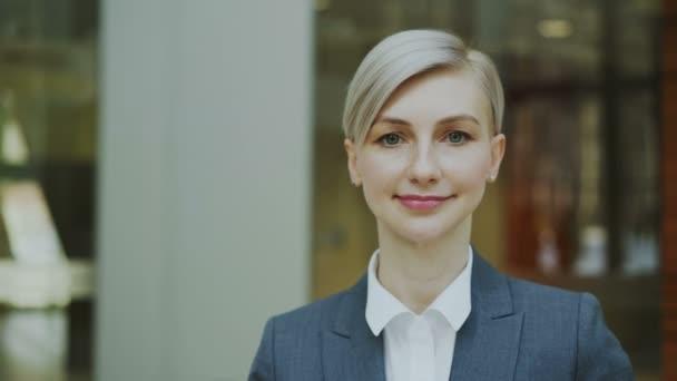Detail portrét úspěšná podnikatelka blondýna usmívá a při pohledu do kamery v moderní kanceláři