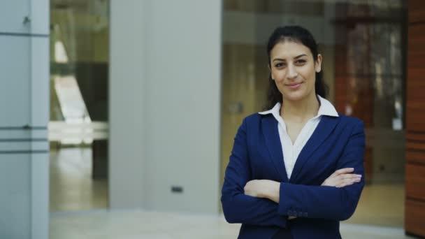 Portrét úspěšná podnikatelka s úsměvem a při pohledu do kamery v moderní kanceláři
