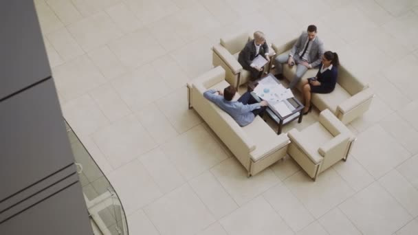Top view of group of business people colleagues discussing financial charts sitting on couchs in lobby at modern business center