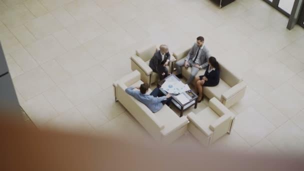 Pohled shora skupiny lidí se spolupracovníky diskutovat finanční grafy na couchs v hale v moderní obchodní centrum