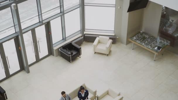 Naklonit dolů pohled shora skupiny lidí se spolupracovníky diskutovat finanční grafy na couchs v hale v moderní obchodní centrum