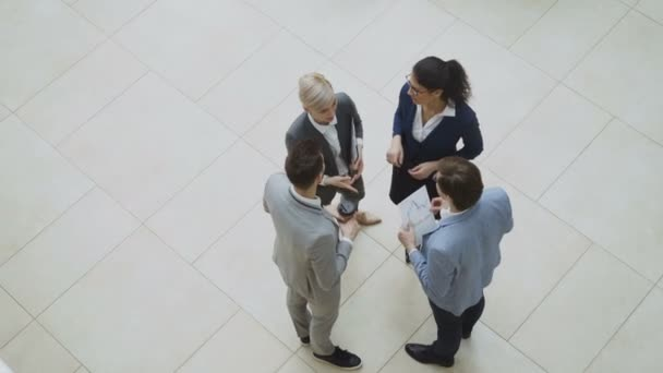 Top view of group of business people in suits discussing financial graphs and then waving hands and smiling looking into camera in lobby of business center