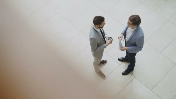 Top view of two businessmen chatting and discussing financial report standing in lobby of business center