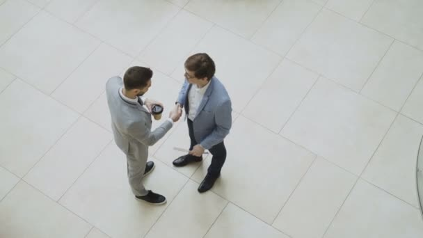 Top view of two businessmen greeting and shaking hands and chatting during coffee break in lobby of business center
