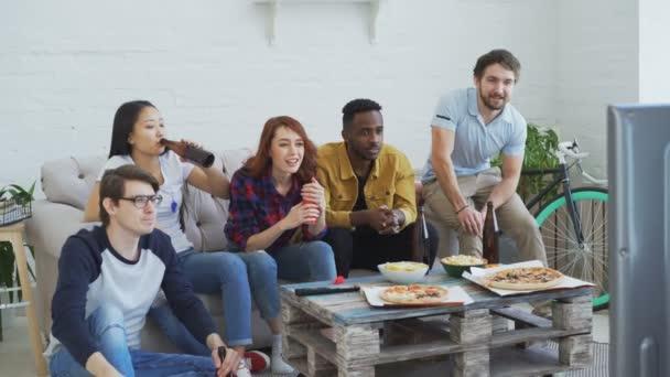 Gruppe junger Freunde Sportübertragungen im Fernsehen zusammen Snacks zu essen und trinken Bier zu Hause passen. Einige von ihnen zufrieden mit ihrer Mannschaft gewinnen aber andere enttäuscht