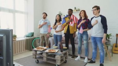 Multi ethnic group of friends sport fans singing national USA anthem before watching sports championship on TV together at home