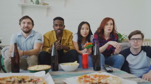 Il gruppo etnico multi di amici sportivi guardando sport partita in Tv insieme celebrante gol della squadra del cuore mentre mangiare spuntini e bere birra a casa