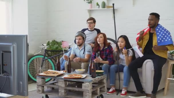 Multi-ethnische Gruppe von Freunden mit Usa National Flaggen beobachten Sport Meisterschaft im Fernsehen zusammen und glücklich über den Gewinn der Lieblingsmannschaft zu Hause