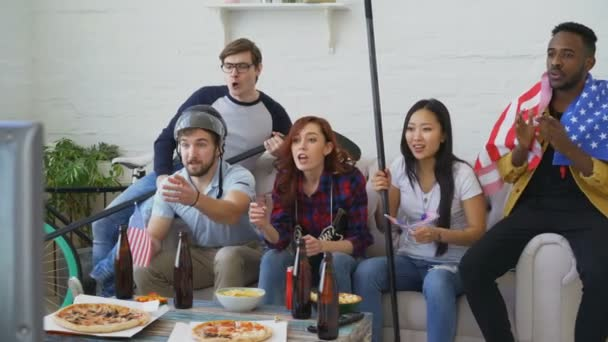 Multi ethnic group of friends sports fans with USA national flags watching winter olympic games on TV together cheering up favourite team at home