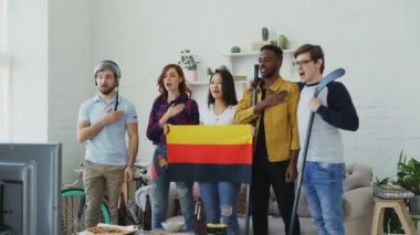 Multi ethnic group of friends listening and singing German national anthem before watching sports championship on TV together at home