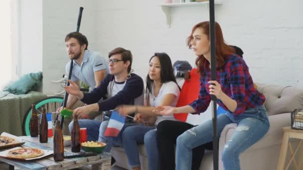 multiethnische Gruppe befreundeter Sportfans mit französischen Nationalflaggen, die gemeinsam ihre Lieblingsmannschaft im heimischen Fernsehen anfeuern