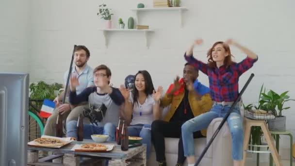 Heterogene Gruppe von Freunden sport Fans mit französischen Nationalflaggen gerade Wintersport-Spiele im Fernsehen zusammen Aufmunterung Lieblingsmannschaft zu Hause