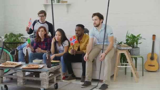 Gruppe junger Freunde Sport-Fans mit norwegischen Landesflaggen Sport Meisterschaft im Fernsehen zusammen und glücklich über den Gewinn der Lieblingsmannschaft zu Hause beobachten