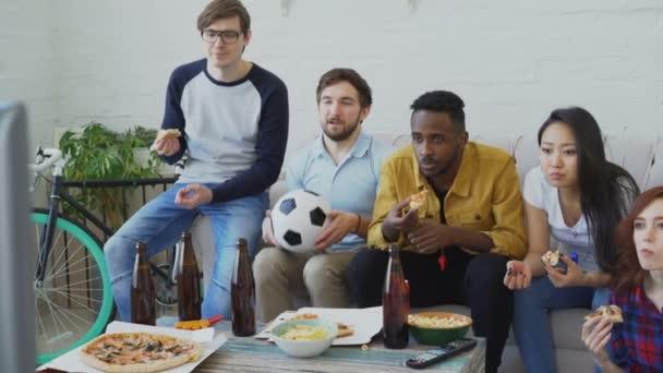 Multi-ethnische Gruppe von Freunden Sport-Fans, die Fußball-EM im Fernsehen zusammen Pizza essen und Bier zu Hause beobachten
