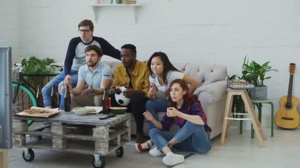 Gruppe junger Freunde Fußballspiel im Fernsehen zusammen Snacks zu essen und trinken Bier zu Hause beobachten. Mädchen sind glücklich mit ihrem Team gewinnen aber Männer enttäuscht