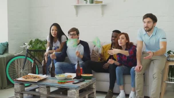 Multi-ethnischen Gruppe von Freunden Sport-Fans mit brasilianische Fahnen gerade Fußball-EM im Fernsehen zu Hause zusammen und Aufmunterung Lieblingsmannschaft