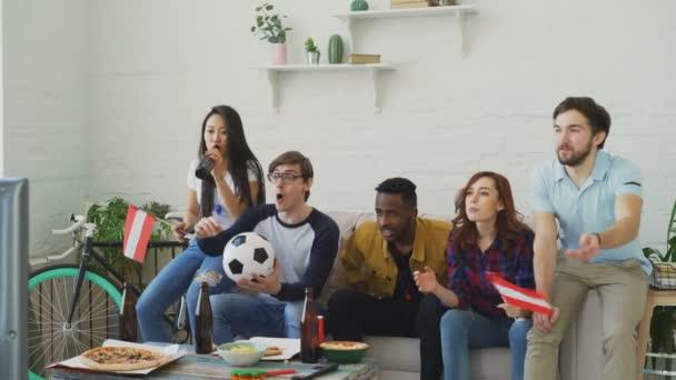 Multi-ethnischen Gruppe von Freunden Sport-Fans mit österreichischen Fahnen gerade Fußball-EM im Fernsehen zu Hause zusammen und Aufmunterung Lieblingsmannschaft