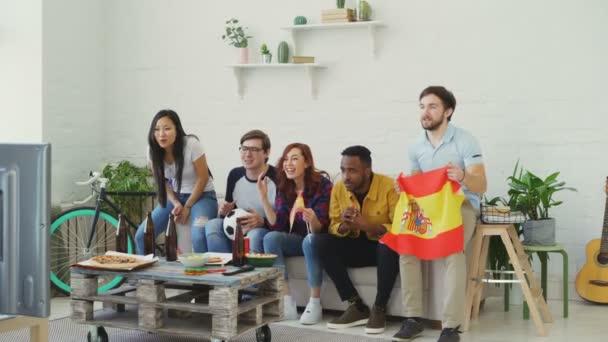 multiethnische Gruppe befreundeter Sportfans mit spanischen Fahnen, die zu Hause gemeinsam die Fußballmeisterschaft im Fernsehen verfolgen und ihre Lieblingsmannschaft anfeuern