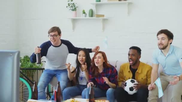 Multi-ethnischen Gruppe von Freunden Sport-Fans mit argentinischen Fahnen gerade Fußball-EM im Fernsehen zu Hause zusammen und Aufmunterung Lieblingsmannschaft
