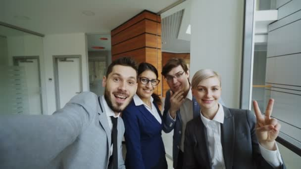 POV of Happy business team taking selfie portrait on smartphone camera and posing for group photo during meeting in modern office