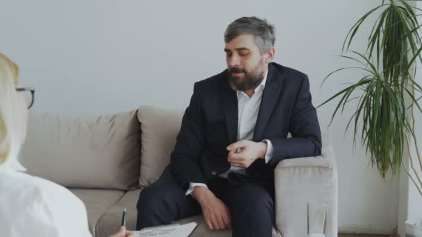 Upset bearded businessman talking about his problems to psychologist in office