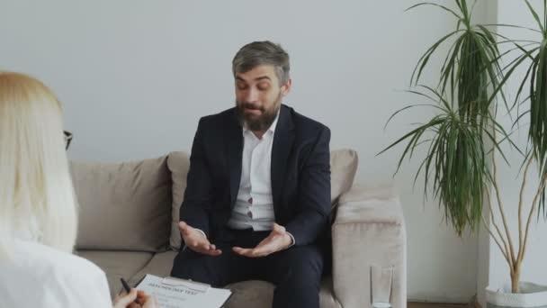 Upset businessman having consultation with female psychologist
