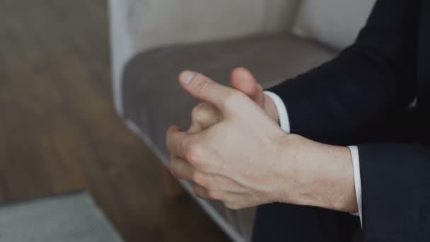 Nahaufnahme eines Geschäftsmannes, der nervös die Hände bewegt, bevor er sich mit einem Psychologen im Büro trifft