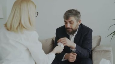 Female psychologist giving paper napkin to crying businessman patient and calm him down in her office