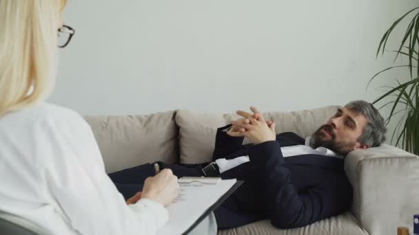 Man lying on sofa talking about his problems with professional female psychotherapist or psychologist in her office