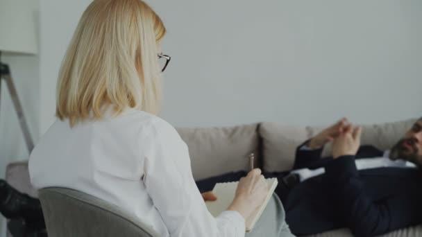 Pan psychoterapeut nebo psaní poznámek zbízka s podnikatelem ležící na pohovce ve své pracovně psycholog