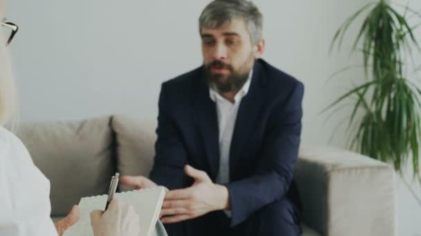Closeup psychoterapeut nebo psaní poznámek zbízka s podnikatelem sedí na pohovce ve své pracovně psycholog