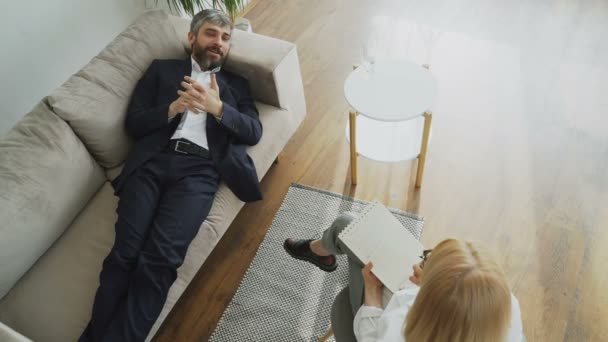 Top view of Man lying on couch talking about his problems with professional female psychotherapist or psychologist in her office