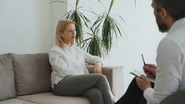 Upset adult woman talking about her family problems with male psychoanalyst in his office