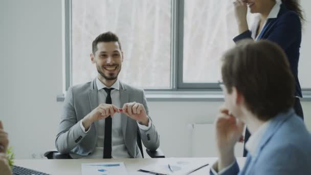 Business male and female colleagues laughing while talking during break sitting at the table in modern office