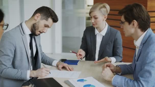 Mladý podnikatel v obleku podepsání smlouvy a potřást rukou s kolegou při firemní právník vysvětlí podrobnosti o partnerství sedí v moderní kanceláři
