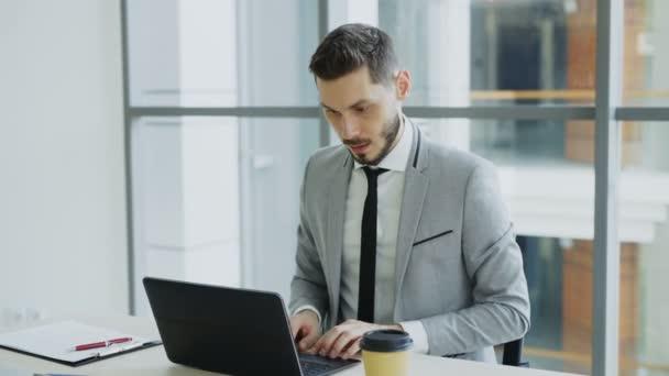 Mladý podnikatel pomocí přenosného počítače dobré zprávy a stát se velmi nadšený a šťastný sedí v moderní kanceláři
