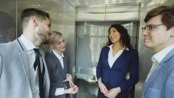 Tracking shot of Businesswomen and businessmen colleagues talking in moving elevator and come out from it and walking in hall in modern business center